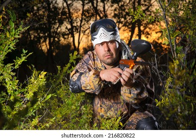 Paintball player on the playing field, hidden in green bushes.