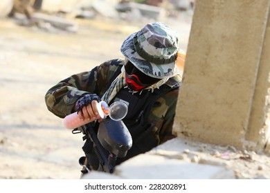 Paintball player in protective uniform and mask reloading a rifle