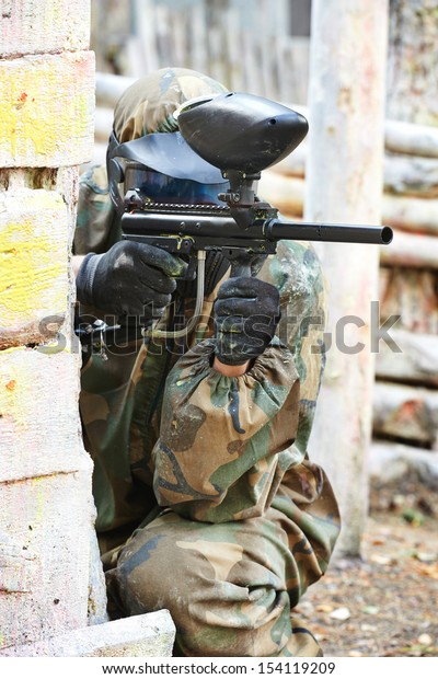 paintball player in protective uniform and mask aiming gun before shooting in summer