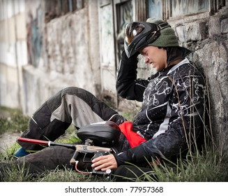 Paintball player relaxing with marker in grunge background