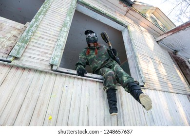 Paintball player sitting on the window sill ready to jump