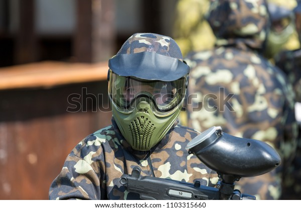 paintball players in a protective form, mask, with gun on the field  before the battle in the summer