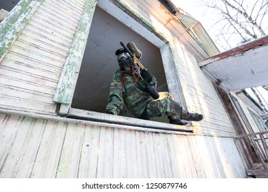 Paintball sportsman extreme jumping from the window of abandoned house