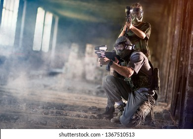 Paintball team together shooting in camouflage wear