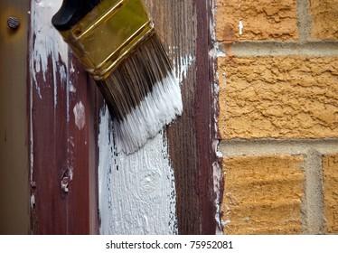 Paintbrush applying primer to wood trim.