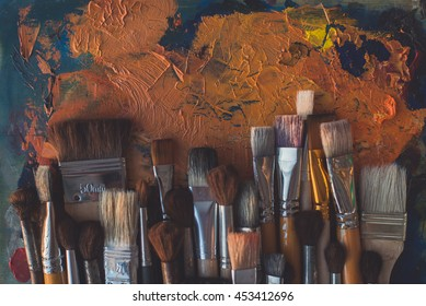 Paintbrush collection on old palette top view. Mixing different oil paints in art studio