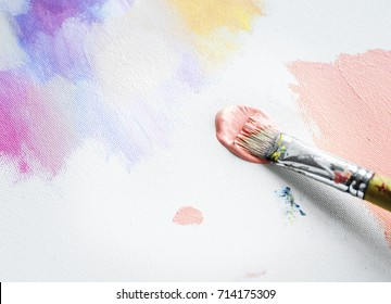 Paintbrush with color on a canvas painting