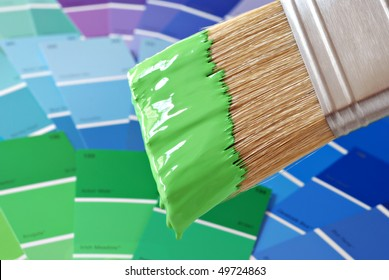 Paintbrush dipped in green paint with color samples in soft focus in background.  Macro with extremely shallow dof.