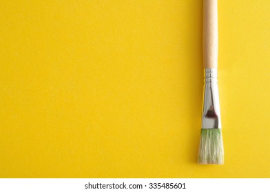 A paintbrush isolated on a yellow background