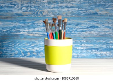Paintbrush in mug in front of a rustic, blue wall in the background