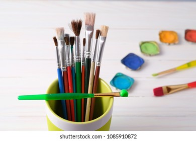 Paintbrush in mug with watercolor paints in the background