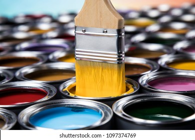 Paintbrush on cans with color