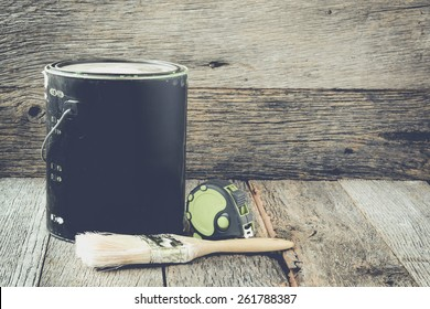 Paintbrush with Paint can and measuring tape on wood background