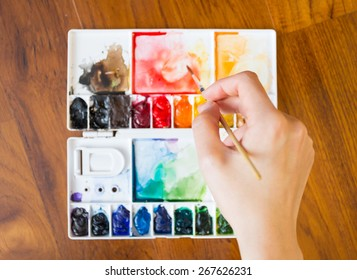 Paintbrush and paint palette with artist's hand holding brush painting colorful mixed watercolor