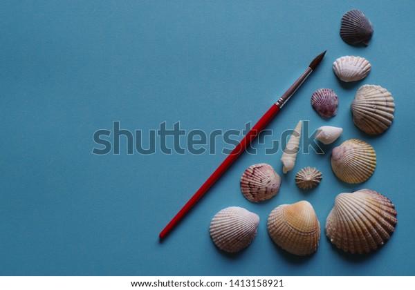 paintbrush-seashells-on-blue-background-
