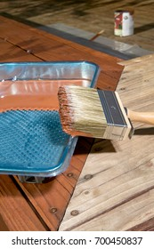 Paintbrush with varnish in a plastic tray on a wooden deck or floor viewed at the corner angle with a tin of lacquer in the background