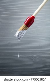 Paintbrush with white paint on a background of old wooden wall. Copy space.