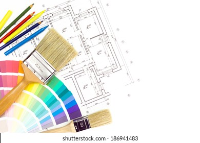 Paintbrushes and colorful paint samples on house plan blueprint background