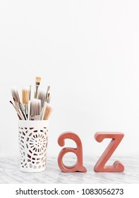 Paintbrushes with metal A and Z letters on marble surface. Art learning or teaching concept.