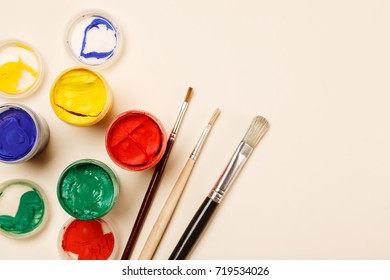 Paintbrushes, open paint jars on a table, top view, copy space