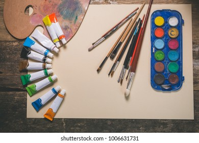 Paintbrushes and palette on wooden table