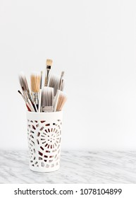 Paintbrushes in a white decorative vase, on marble surface.