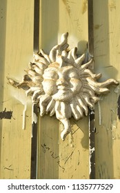 painted 3-D stylized vintage sun symbol human facial features on outdoor street wall