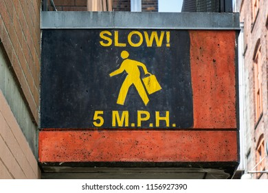Painted 5 mph speed limit street sign for pedestrians requested to slow down in the streets of Seattle, Washington, USA.