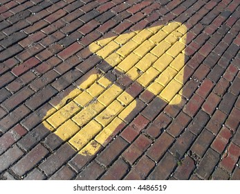 Painted arrow on brick road