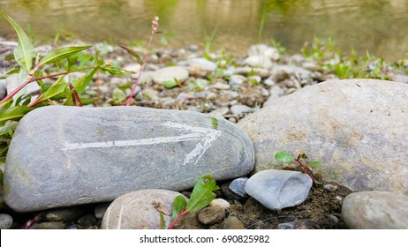 Painted arrow on stone show direction on dry rocks close to river side