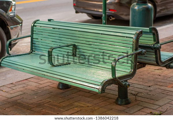 Painted bluish green wood slat city sidewalk bench with black metal trim and arm rests with sun slightly reflecting off painted seat. background has parts of 2 parked cars, curb and brick pavers.