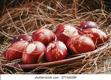Painted brown onion peel Easter eggs with a pattern of grass on a clay plate in the dry straw in a country style, selective focus