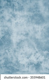 Painted canvas or muslin fabric cloth studio backdrop or background, suitable for use with portraits, products and concepts. Light blue painted design.