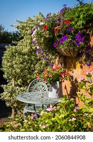 A painted cast iron garden chair and table against a sunny English garden wall with trailing and colourful petunias and a decorative watering can.