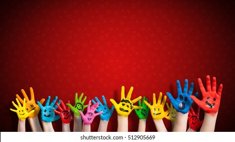 painted children hands with smiley in front of christmas background