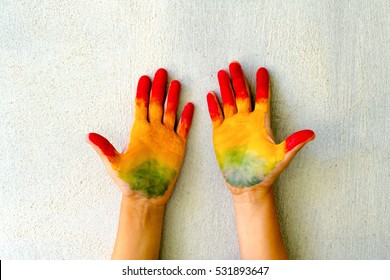 painted childs hands raised up