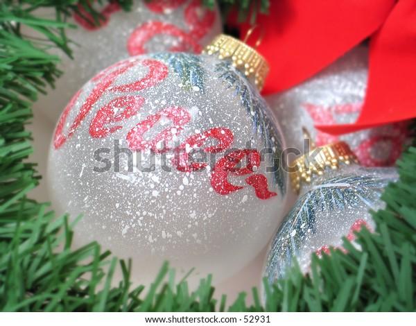 Painted Christmas bulbs under a wreath. Focus on Peace bulb.