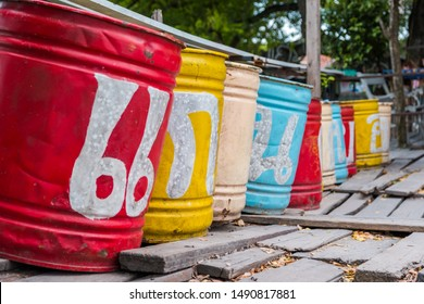 """The painted color on a old buckets in Thai word mean """"Grand Canyon"""". The buckets in front of entrance the Grand Canyon in Thailand. The colorful tanks on the old wood plates."""