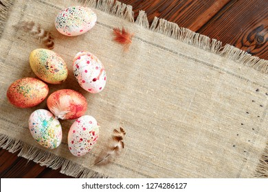 painted colored Easter eggs on canvas on dark wooden background