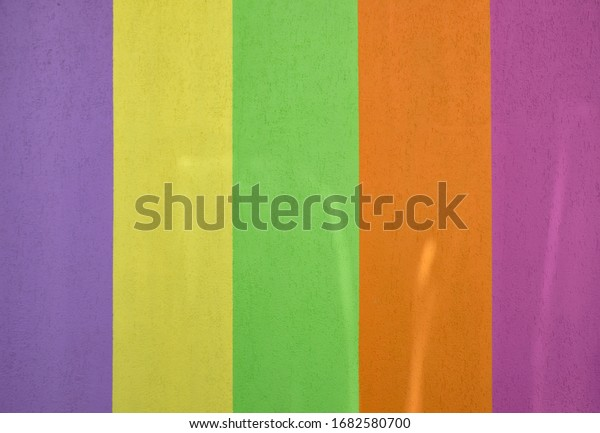 Painted concrete wall with bright pastel vertical stripes with touches of sunlight