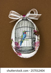 Painted Easter egg with the hummingbird in the cage. Spring theme.