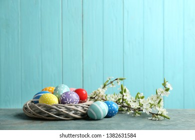 Painted Easter eggs in nest and blossoming branches on table against color background. Space for text