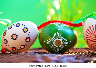 Painted easter eggs in the wicker basket in the grass.