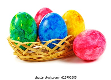 Painted Easter eggs in wicker basket on white background