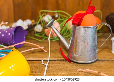 painted egg with a bow. watering can and buckets. happy Easter composition