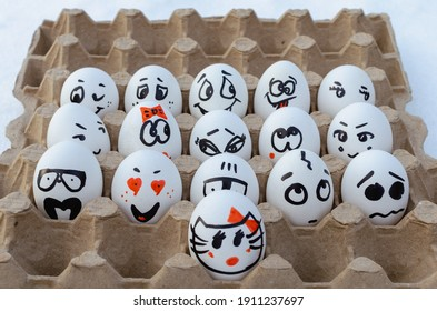 Painted eggs with faces and emotions in egg tray.