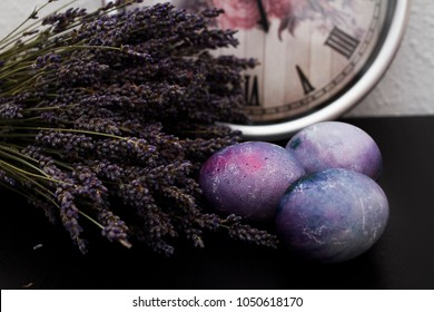 Painted eggs on a black background with a bouquet of lavender and a clock