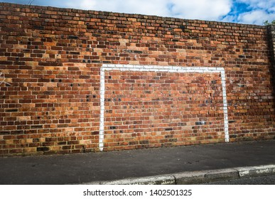 Painted footbal goalpost on a wall in a street.