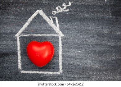 Painted House with Red Heart on a Black Chalkboard. Top View with Copy Space. Love Concept.