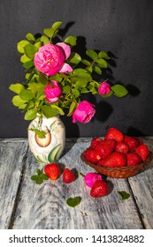 In a painted jug there are branches of lilac roses and jasmine leaves. Near in a plate strawberries are poured. Her berries are on the table. Still life on a dark background.